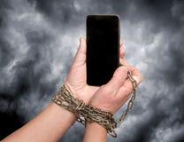 De telefoon wordt geketend aan de handen op de donkere dramatische hemel als achtergrond Afhankelijkheid van mobiele phone_ stock fotografie