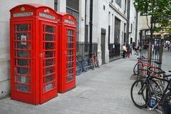 De telefoondozen en fietsen van Londen Stock Afbeeldingen
