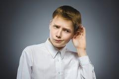 De teleurgestelde jongen luistert kindhoorzitting iets, hand aan oorgebaar royalty-vrije stock afbeeldingen