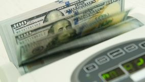 De tellende machine telt vele rekeningen voor honderd Amerikaanse dollars van een nieuwe steekproef Het tellen van het geld stock footage