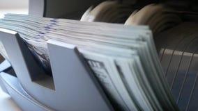 De tellende machine van het contant geldgeld De bankbiljetteller telt honderd dollarsrekeningen stock video