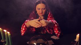 De teller van het zigeunerfortuin bij de lijst door kaarslicht leest de toekomst in een magisch kristal stock video