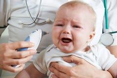 De Temperatuur van verpleegsterstaking crying baby met Digitale Thermometer royalty-vrije stock fotografie