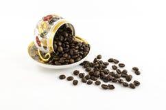 De ten val gebrachte die kop van de porseleinkoffie met koffiebonen op wit worden geïsoleerd Stock Foto