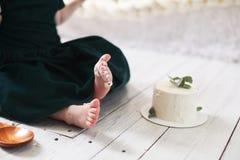 De tenen van het kind in de cake romen op de achtergrond van witte houten vloer en witte cake af stock foto