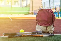 De tennisrackets met een bal dichtbij de sport doen met materiaal op het hof op de zomerdag in zakken stock foto