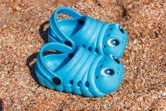 De tennisschoenen van blauwe kinderen op het strand Stock Fotografie