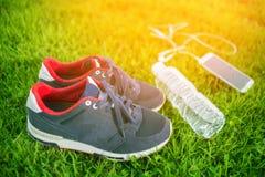 De tennisschoenen van sportenschoenen en fles water op een vers groen gras De zon` s stralen Sporten openlucht royalty-vrije stock fotografie