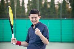 De tennisspeler drukt zijn overwinning in het spel uit stock afbeeldingen