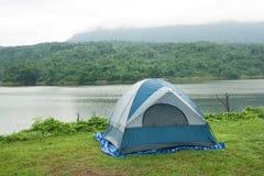 De tent op het gras, met achtergronden is reservoirs stock foto's