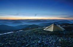 De tent van de toerist in de rotsachtige bergen en de eerste ster Royalty-vrije Stock Fotografie
