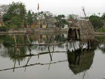 De tenten met met stro bedekte daken worden uitgespreid op het meer stock foto