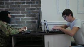 De terrorist in zwart masker betaalt steekpenningsgeld aan computerhakker, hand aan stock video