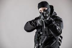 But de terroriste avec l'arme à feu sur le fond gris photos stock