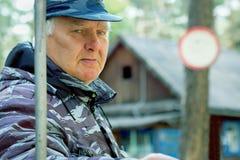 De teruggetrokken oude mens bewaakt openluchtgrondgebied Noodzaak van extra inkomens stock foto