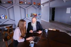 De teruggetrokken oude mens vraagt om raad over nieuwe technologie bij beautifu Royalty-vrije Stock Foto