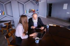 De teruggetrokken oude mens vraagt om raad over nieuwe technologie bij beautifu Royalty-vrije Stock Fotografie