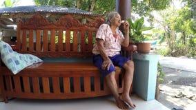 De teruggetrokken zitting van de landbouwbedrijf oude vrouw op bank die brood eten stock video