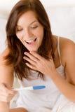 De test van de zwangerschap - gelukkige verraste vrouw stock afbeeldingen
