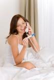 De test van de zwangerschap - gelukkige vrouw op telefoon stock afbeelding