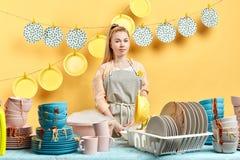 De tevreden aantrekkelijke vrouw met vriendschappelijke blik maakt keuken schoon royalty-vrije stock foto
