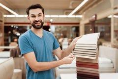 De tevreden gebaarde mens kiest kleur op kleurenpalet Het selecteren van kleur van matras op de gids van het kleurenpalet Stock Fotografie