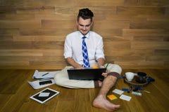De tevreden jonge mens in grappige kleren zit op de vloer tegen een muur en werkt met laptop stock foto's