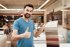 De tevreden mens kiest kleur op kleurenpalet Het selecteren van kleur van matras op de gids van het kleurenpalet Royalty-vrije Stock Foto's