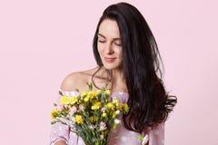 De tevreden opgetogen donkere haired jonge vrouw ruikt prettige geur van bloemen, gekleed in modieuze kleren, heeft gezonde huid, stock afbeelding