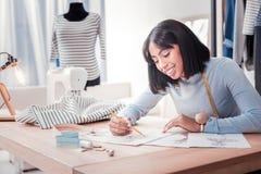 De tevreden schetsen van de ontwerpertekening voor nieuwe kleding stock fotografie