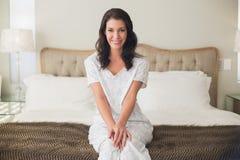 De tevreden vrij bruine zitting van de haarvrouw op een bed Royalty-vrije Stock Afbeelding