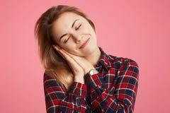 De tevreden vrij jonge vrouw leunt bij handen, heeft prettige gezonde droom, rust voor minuut na slapeloze nacht, gevierde verjaa Stock Afbeelding