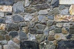 De textuur, de achtergrond van de muur voerde met natuurstenen van verschillende vormengrootte en kleuren Royalty-vrije Stock Foto