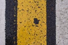 De textuur van de asfaltweg met gebarsten witte en gele streep Stock Foto's
