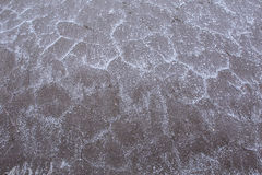 De textuur van de oppervlakte van de zout-gebarsten kust met grote kristallen van zout Stock Fotografie