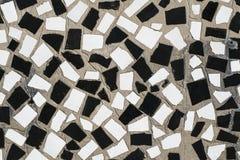 De textuur van de oude muur is verfraaid met mozaïekplakken van ceram Stock Foto
