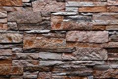De textuur van de steen grijze bruine oranje muur natuurlijke kleur als achtergrond Stock Fotografie