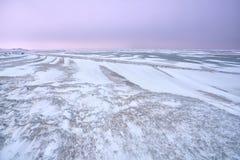 De textuur van de windsneeuw door bevroren strand door Noordzee Stock Foto