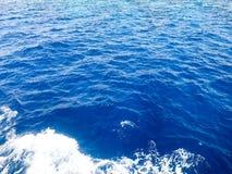 De textuur van een borrelende blauwe natte natuurlijke overzees van zuiver water met golven, bellen, wit schuim, plonsen, plonsen Stock Afbeeldingen