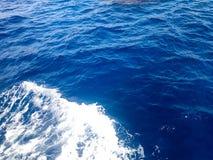 De textuur van een borrelende blauwe natte natuurlijke overzees van zuiver water met golven, bellen, wit schuim, plonsen, plonsen Royalty-vrije Stock Afbeeldingen