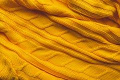 De textuur van een gebreide wollen stof Achtergrond om de winterlay-outs, Kerstkaarten, banners tot stand te brengen Brei gele sw Stock Afbeeldingen