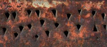 De textuur van een roestige metaaloppervlakte met driehoekige gaten stock foto's
