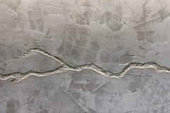 De textuur van de grijze concrete muur is verfraaid met een diepe barst van zilveren kleur stock afbeeldingen