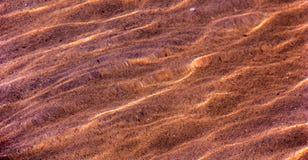 De textuur van het zand op de bodem door het water stock afbeelding