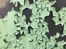 De textuur van de oude sjofele turkooise lichtgroene schilverf met barsten en krassen op de roestige metaalmuur Achtergrond royalty-vrije stock afbeelding