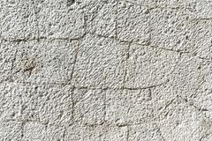 De textuur van oude witte steenmuur met barsten sluit omhoog stock foto