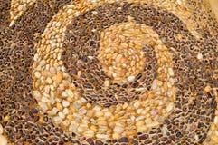 De textuur van de steenmuur, de weg van kleine ronde en ovale stenen met samengevatte lijnen van spiraalvormige patronen met zand royalty-vrije stock foto's