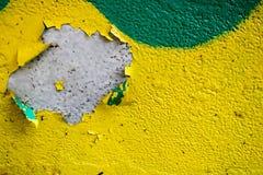 De textuur van twee kleurt gele en groene oude sjofele concrete muur met bolvormige schil varicoloured verf, kuilen en patronen stock foto's