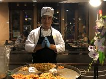 De Thaise chef-kok in een kostuum vouwde zijn handen Namaste, bereidt hij een nationale schotel van zeevruchten, rijstnoedels en  royalty-vrije stock foto