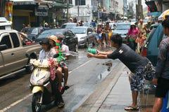 De Thaise kerel werpt water aan meisjes op een fiets Stock Fotografie